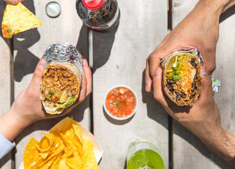 two people holding burritos