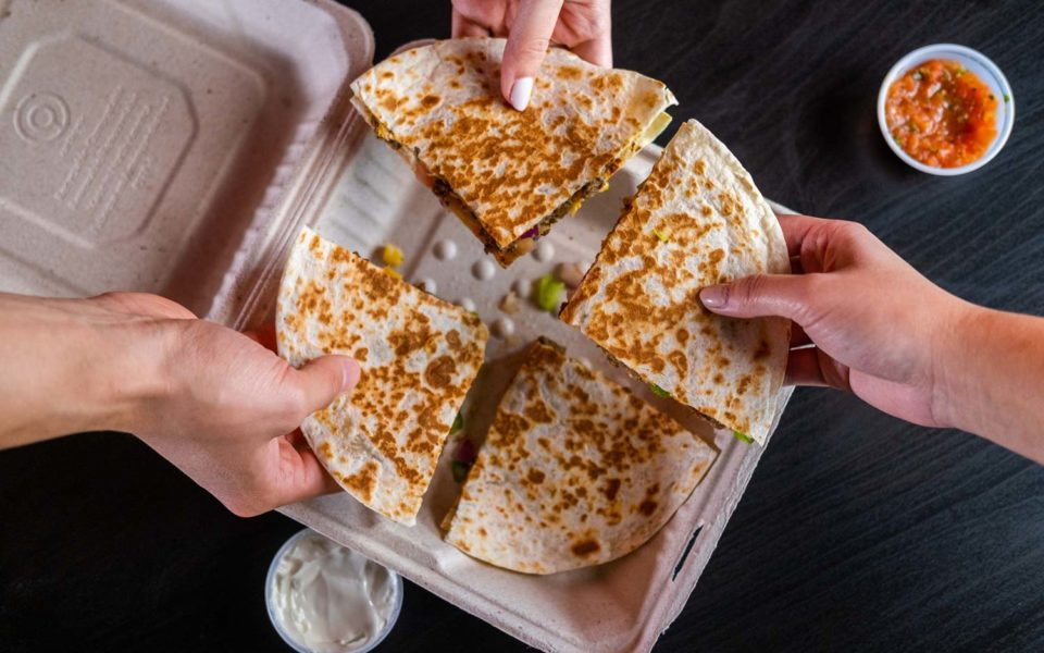 three people holding pieces of a quesadilla